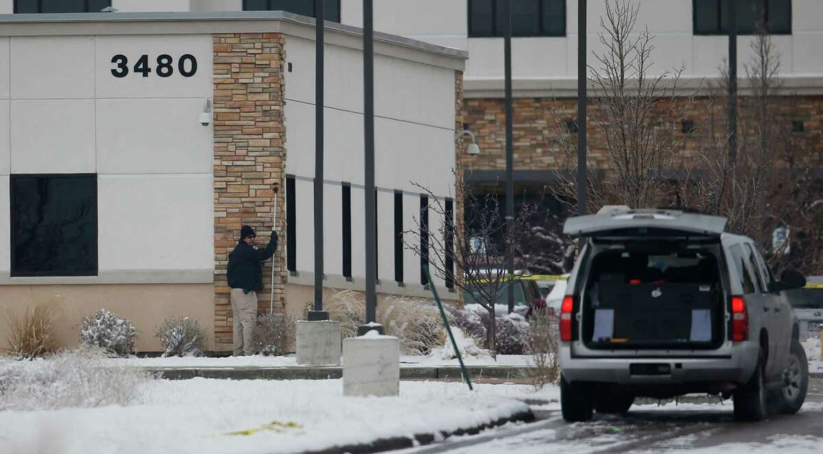 A police investigator holds up a measure along the wall of a Planned Parenthood clinic building, while gathering evidence from the Friday shooting outside the clinic Sunday, Nov. 29, 2015, in northwest Colorado Springs, Colo. (AP Photo/David Zalubowski) ORG XMIT: CODZ127