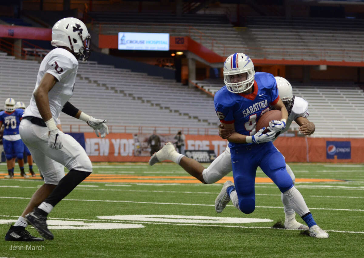 Saratoga running back Robert Haughton is tackled by Aquinas linebacker Damon Burton during the Class AA State Championship, Sunday, Nov. 30, 2015, in Syracuse, N.Y. (Jenn March/Special to the Times Union)