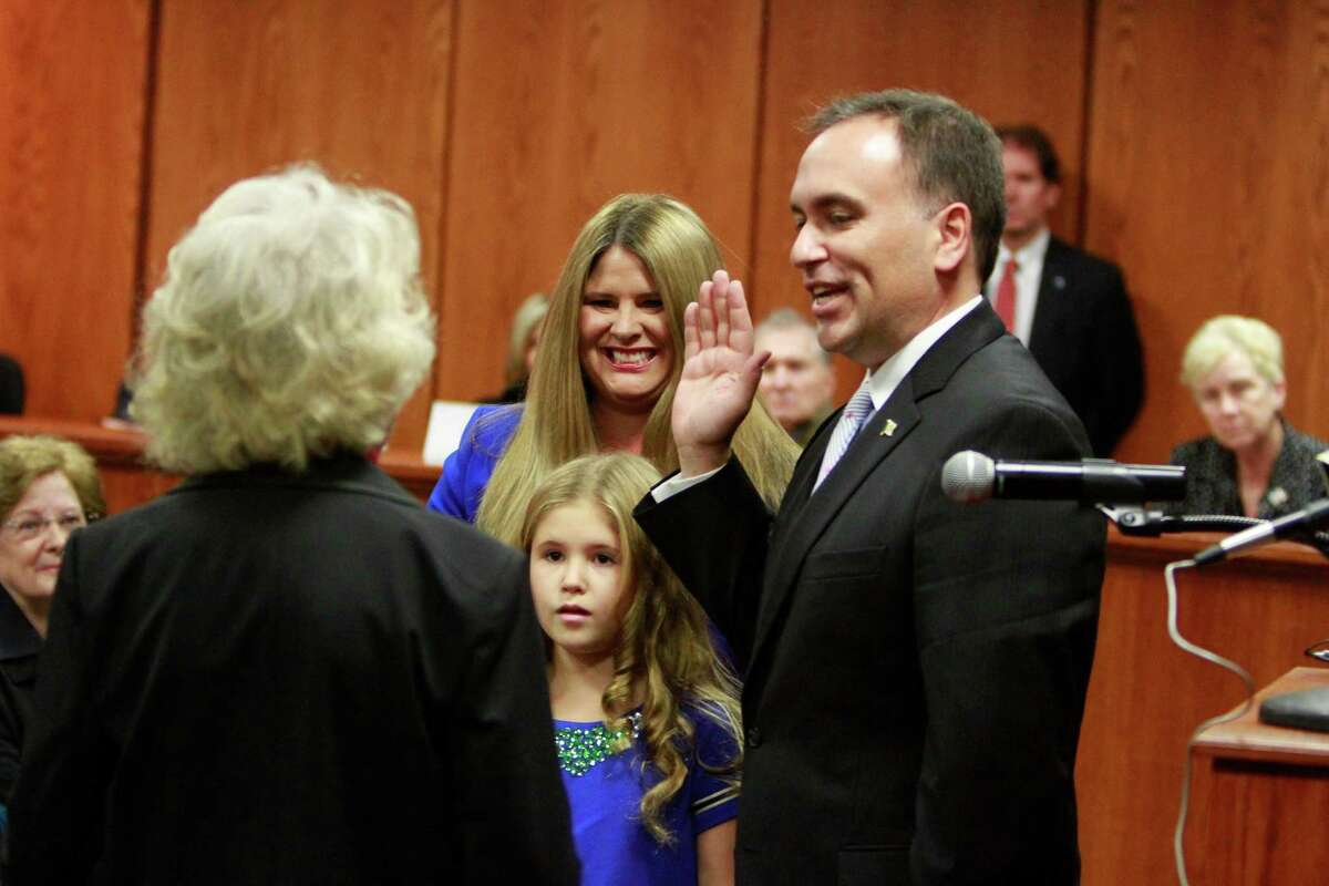 First Selectman Peter J. Tesei stands with his family as Rebecca S. Breed administers the oath of office during a swearing-in ceremony at the Greenwich Town Hall on Sunday.