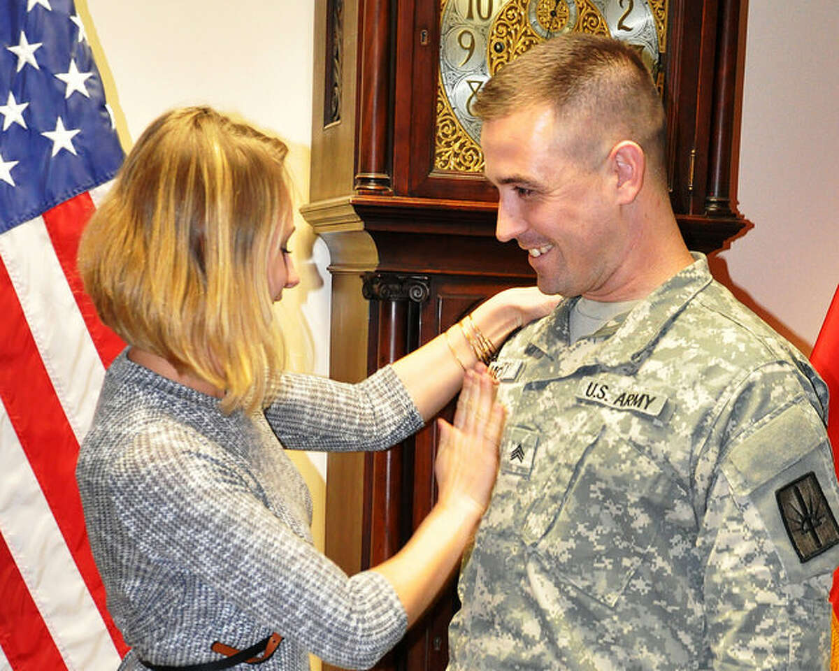 Division of Military and Naval Affairs Amanda McCarty pins new sergeant rank on her husband, Sgt. Lucian McCarty, during a promotion ceremony in Latham.