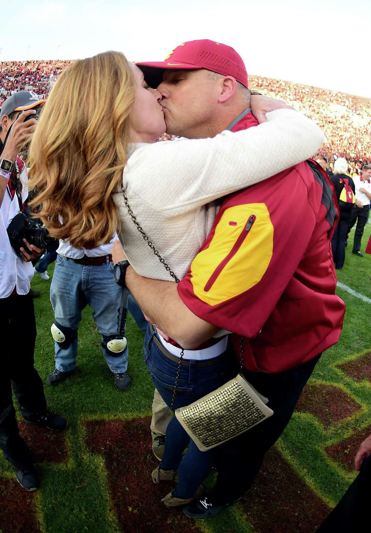 LOS ANGELES, CA - NOVEMBER 28: Head coach Clay Helton of the USC Trojans and his wife Angela kiss after a 40-21 win over the UCLA Bruins at Los Angeles Memorial Coliseum on November 28, 2015 in Los Angeles, California.