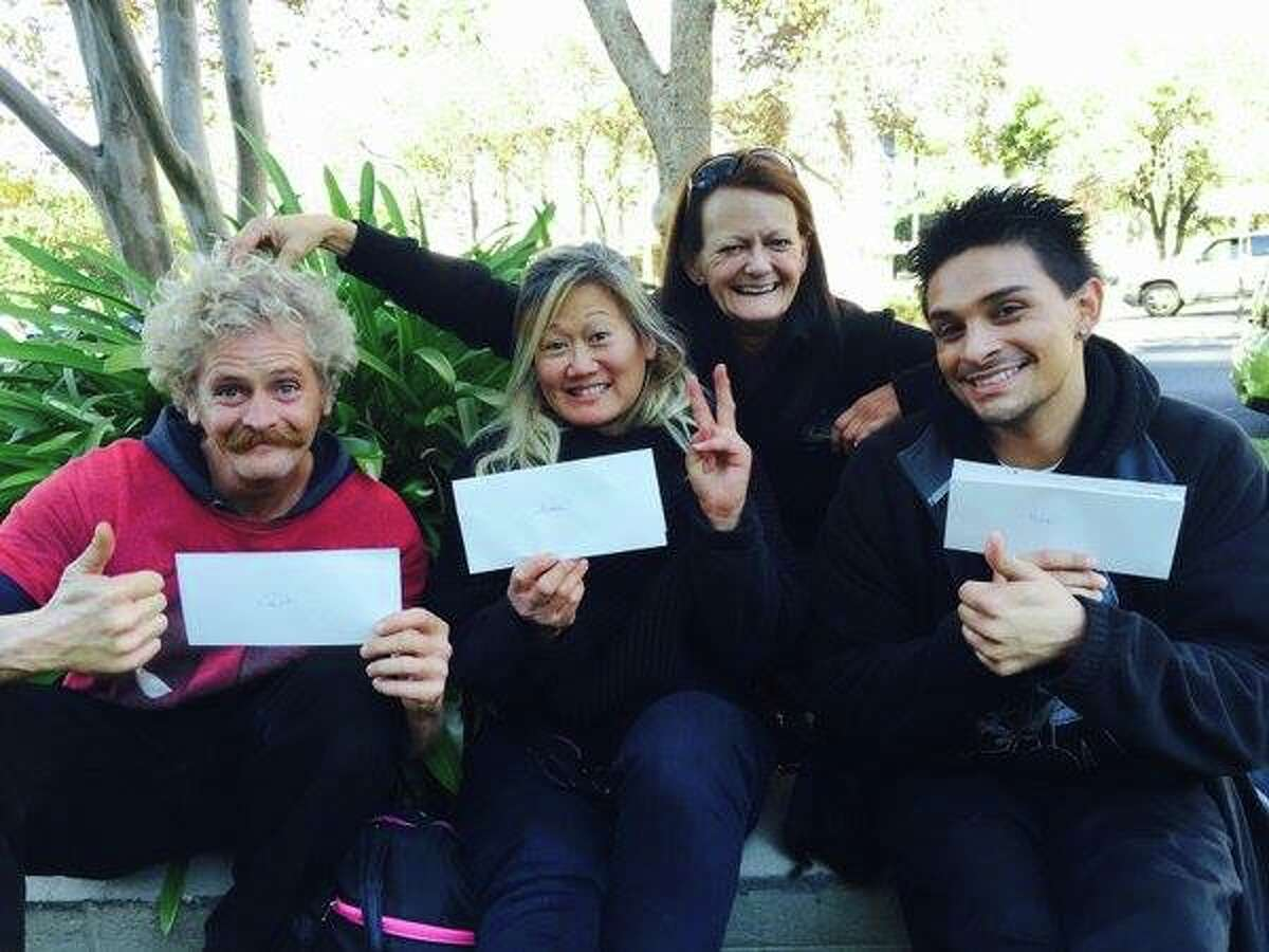 Homeless or formerly homeless workers are holding their first paycheck from the Kartma Street Café.