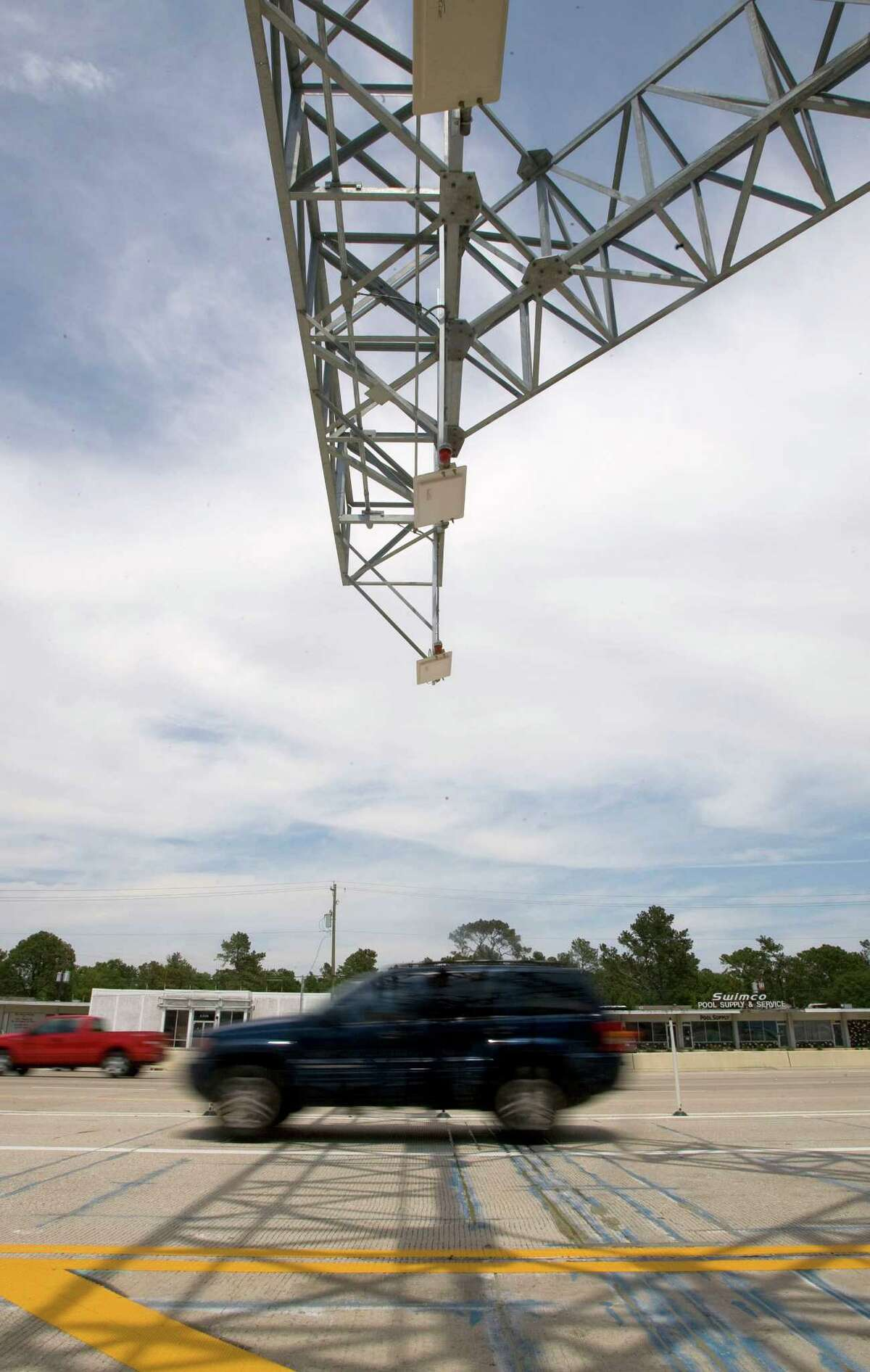 A vehicle passes through an electronic toll collection point during a media tour of the Katy Managed Lanes on April 15, 2009.