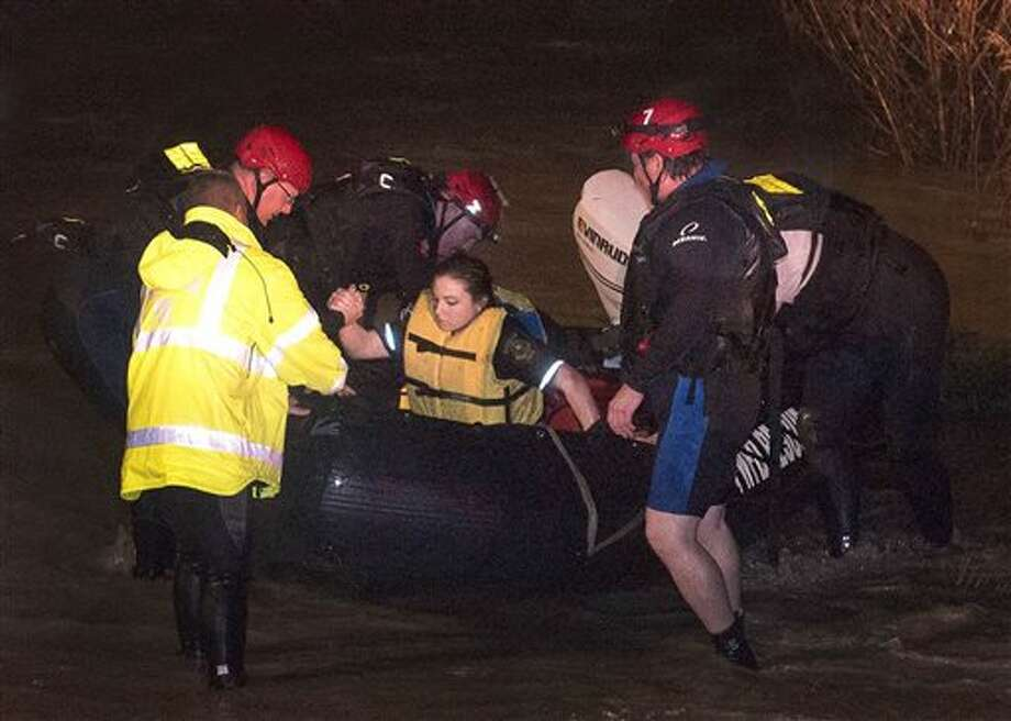 Firefighters assist Tarrant County Sheriff's Deputy Krystal Salazar after they rescued her from the raging waters of Deer Creek early Friday, Nov. 27, 2015, in Fort Worth, Texas. Salazar had gone into the water to attempt to rescue two other people that were swept away in the rushing waters, according to the Fort Worth Star-Telegram. The search continued for the missing people. (Glen E. Ellman/Star-Telegram via AP)  MAGS OUT; (FORT WORTH WEEKLY, 360 WEST); INTERNET OUT; MANDATORY CREDIT Photo: Glen E. Ellman, Associated Press / Star-Telegram