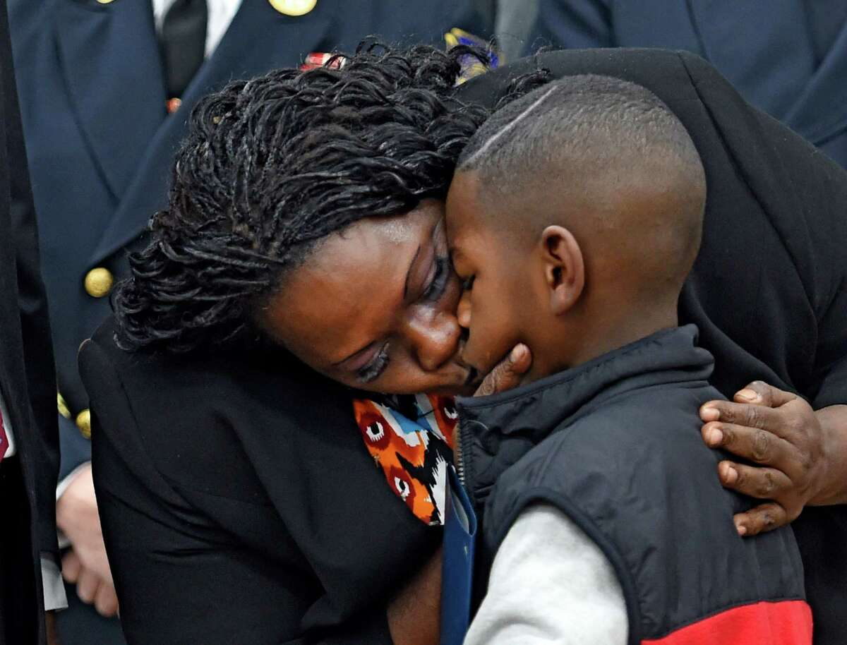 Avery Moses gets a kiss from his very proud mother Lynette Moses, before a ceremony at the South Station of the Albany Fire Department to honor him for his heroism Monday morning Nov. 30, 2015 in Albany, N.Y. Avery was honored for alerting his parents to a fire that took their home in early November of this year. (Skip Dickstein/Times Union)