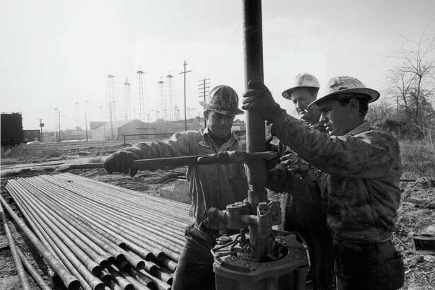 circa 1967: Men fit pipes for oil drilling, Texas, late 1960s.