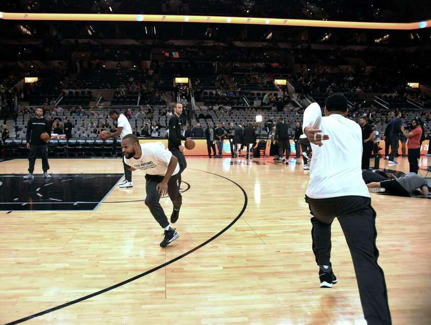 Danny Green, right, and Patty Mills of the San Antonio Spurs pretend to run a football play during warmups before the team's game against the Dallas Mavericks at the AT&T Center on Wednesday, Nov. 25, 2015.