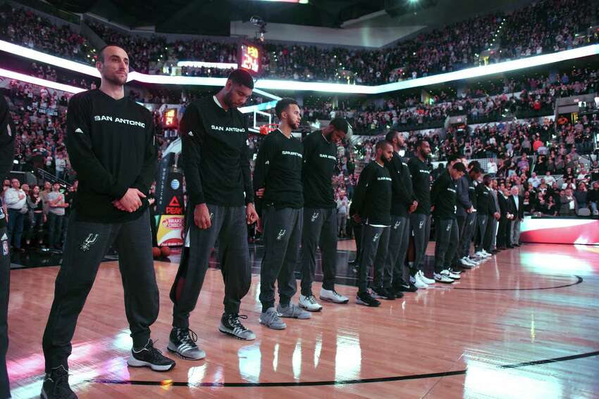 Manu Ginobili, left, Tim Duncan, Kyle Anderson and other members of the San Antonio Spurs pay respects during playing of the Star-Spangled Banner before the team's game against the Dallas Mavericks in NBA action at the AT&T Center on Wednesday, Nov. 25, 2015.