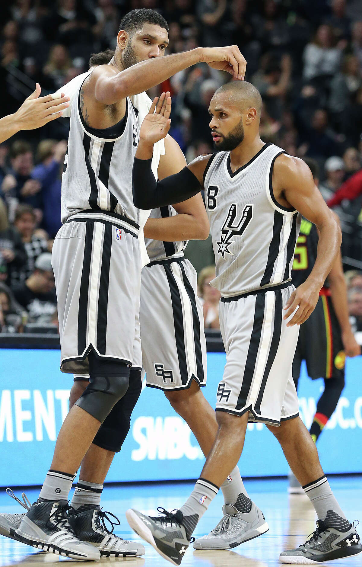 Patty Mills gets a unique congratulations from Tim Duncan as the Spurs play the Atlanta Hawks at the AT&T Center on November 28, 2015.
