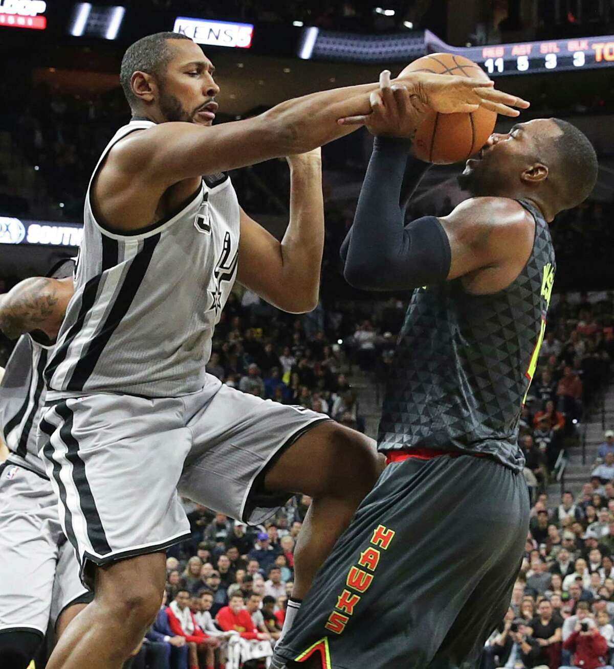 Boris Diaw jams the ball back in the face of Paul Millsap in the first half as the Spurs play the Atlanta Hawks at the AT&T Center on November 28, 2015.