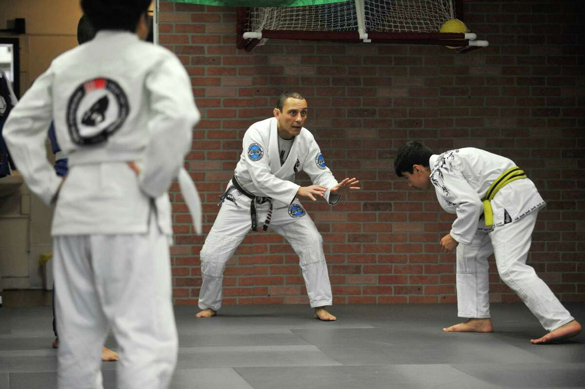 Cesar Pereira reminds the students in his fundamentals class to keep their hands up, but not as high as karate teaches, during a class at Carlson Gracie Brazilian Jiu Jitsu on East Main Street.