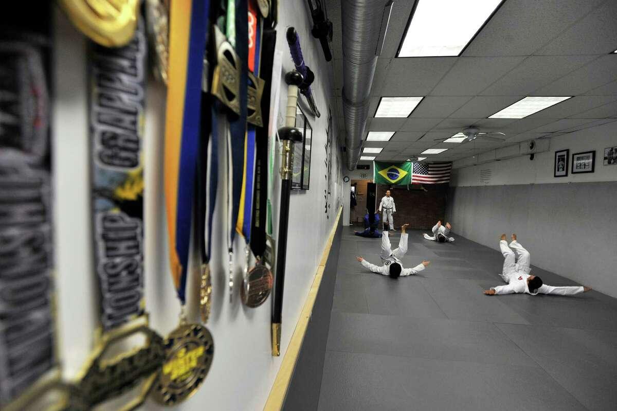 Students in Cesar Pereira's fundamental jiu jitsu class work on the proper way to fall and protect your head at Carlson Gracie Brazilian Jiu Jitsu.