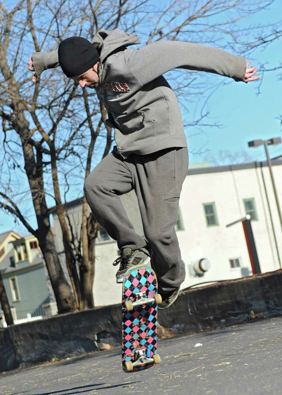Joe Sankovich of Schenectady performs a trick on his skateboard in a parking lot behind his home on Monday, Nov. 30, 2015 in Schenectady, N.Y. (Lori Van Buren / Times Union)