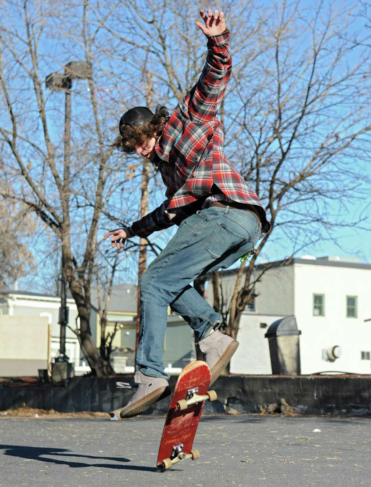 Josh Harris of Schenectady performs a trick on his skateboard in a parking lot behind his home on Monday, Nov. 30, 2015 in Schenectady, N.Y. (Lori Van Buren / Times Union)
