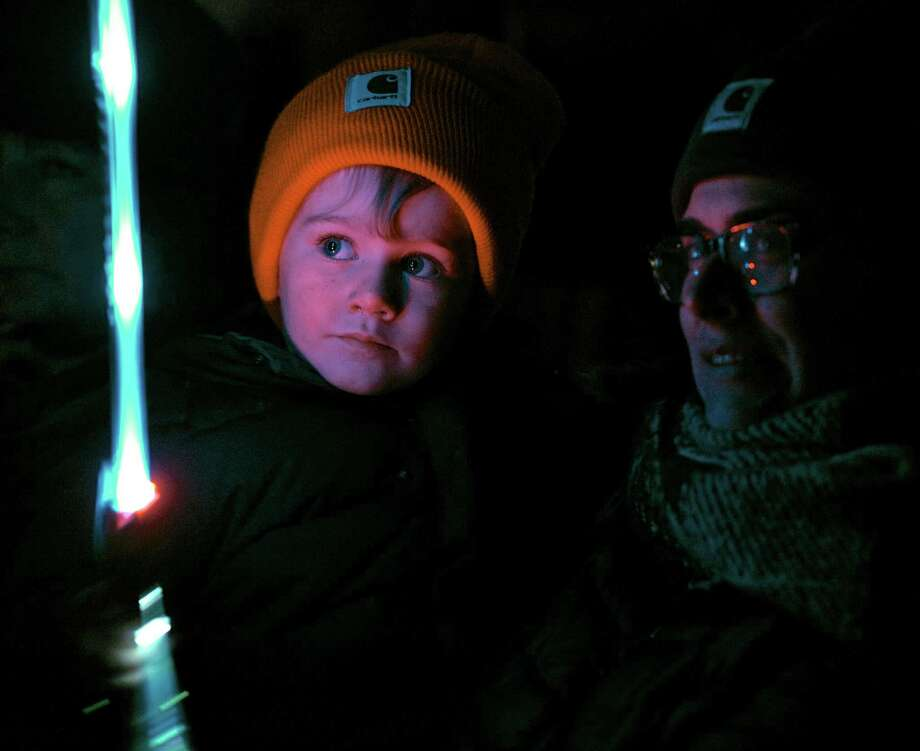 Coleman Cynamon-Ferris, 3, of Sherman, is illuminated by his light saber as he waits with his mother Lauren to visit with Santa during the Festival of Lights on the village green, in New Milford. Saturday, night, November 28, 2015, in New Milford, Conn. Photo: H John Voorhees III / Hearst Connecticut Media / The News-Times