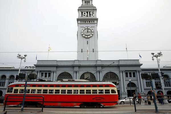 A Muni streetcar drives past the Ferry Building on The Embarcadero in San Francisco, California, on Monday, Nov. 30, 2015.
