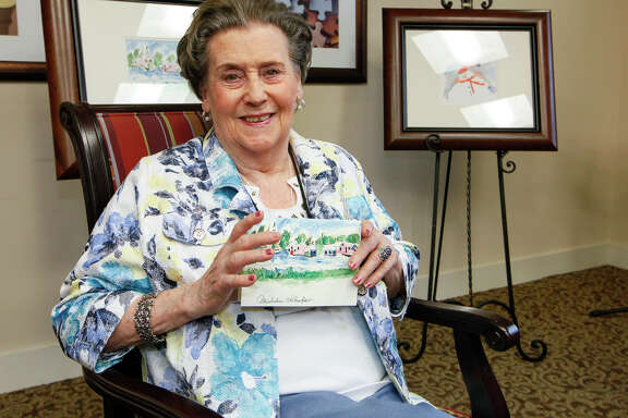 """Micheline """"Mickey"""" Ohlenforst, a resident at the Franklin Park Stone Oak Assisted Living facility, with the Christmas card from the local chapter of the Alzheimer's Association featuring a snow scene she painted, on Dec. 9, 2013."""