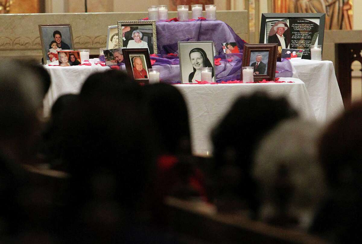 Photographs are placed on a table in remembrance of those lost to Alzheimer's disease during the 11th Annual Candlelight Remembrance Service by the Alzheimer's Association at the Chapel of the Incarnate Word on Nov. 27, 2012. About 100 people took part in the event called