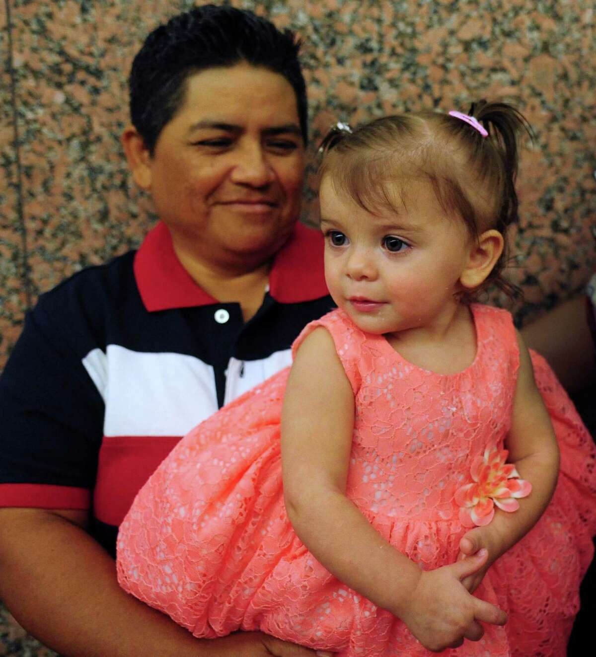 Leticia Ruiz holds Ski Ruiz, a girl that she and her partner, Sabrina Ruiz, adopted during a mass adoption ceremony in the Bexar County Courthouse on Aug. 8, 2014. Child Advocates San Antonio and Child Protective Services representatives attend the monthly event.