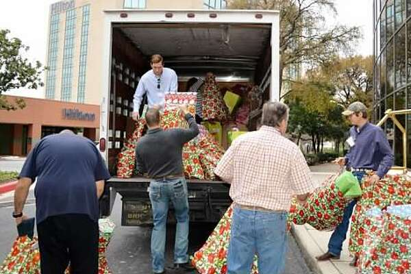 Christy's Hope supporters load Christmas presents destined for the Battered Women and Children Shelter in 2014. They are (from left) Kirk Jorgensen, Rane Pearson (in truck), Jeff Eigel, Jace Pearson and Colt Pearson.