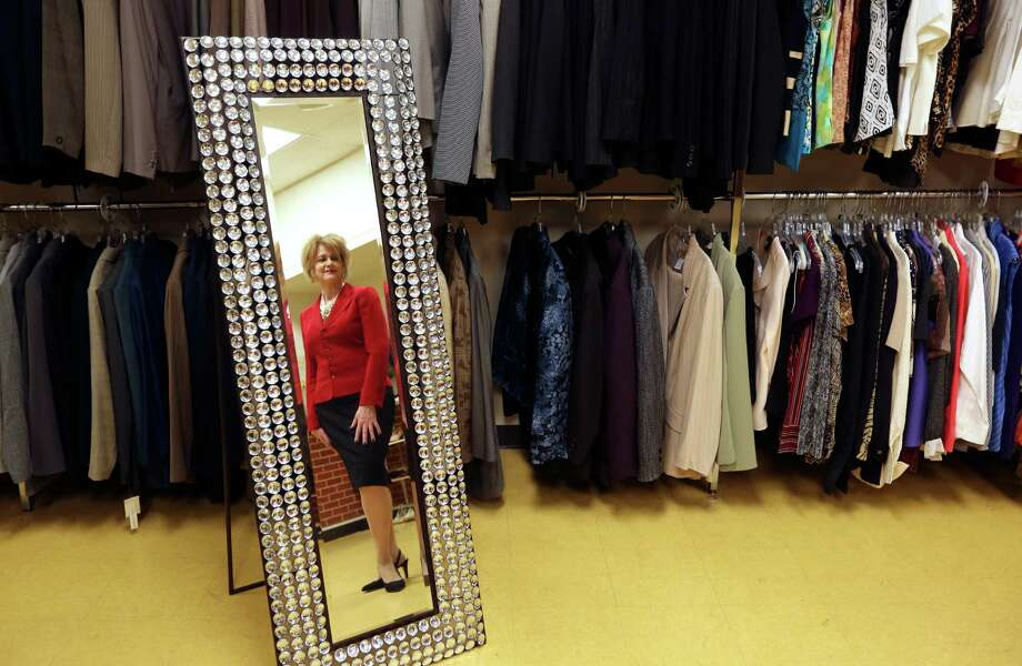 Pamela Taylor poses in the Mirror of Transformation at her Dress For Success agency that helps victims of domestic violence find jobs and break out of poverty. Taylor said the mirror got its name from the way clients react when they see themselves in nice clothes, often for the first time ever. Photo: William Luther /San Antonio Express-News / © 2015 San Antonio Express-News