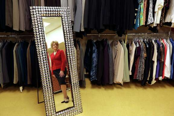 Pamela Taylor poses in the Mirror of Transformation at her Dress For Success agency that helps victims of domestic violence find jobs and break out of poverty. Taylor said the mirror got its name from the way clients react when they see themselves in nice clothes, often for the first time ever.