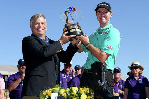 Boerne's Jimmy Walker receives the championship trophy from Lane Riggs, Executive Vice President of Refining Operations with Valero, after winning the Valero Texas Open at TPC San Antonio on Sunday, March 29, 2015.