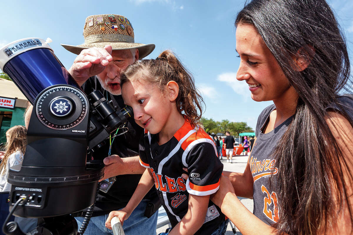Jim Schwartzott (from left) helps Taylor Krantz, 6, look at the sun through a Meade XC90 telescope with a Kendrick filter as her mother, Christina Krantz, looks on during the Girls Inc. of San Antonio's 7th annual Rockit into The Future Science Festival presented by Rackspace Hosting on April 6, 2013.