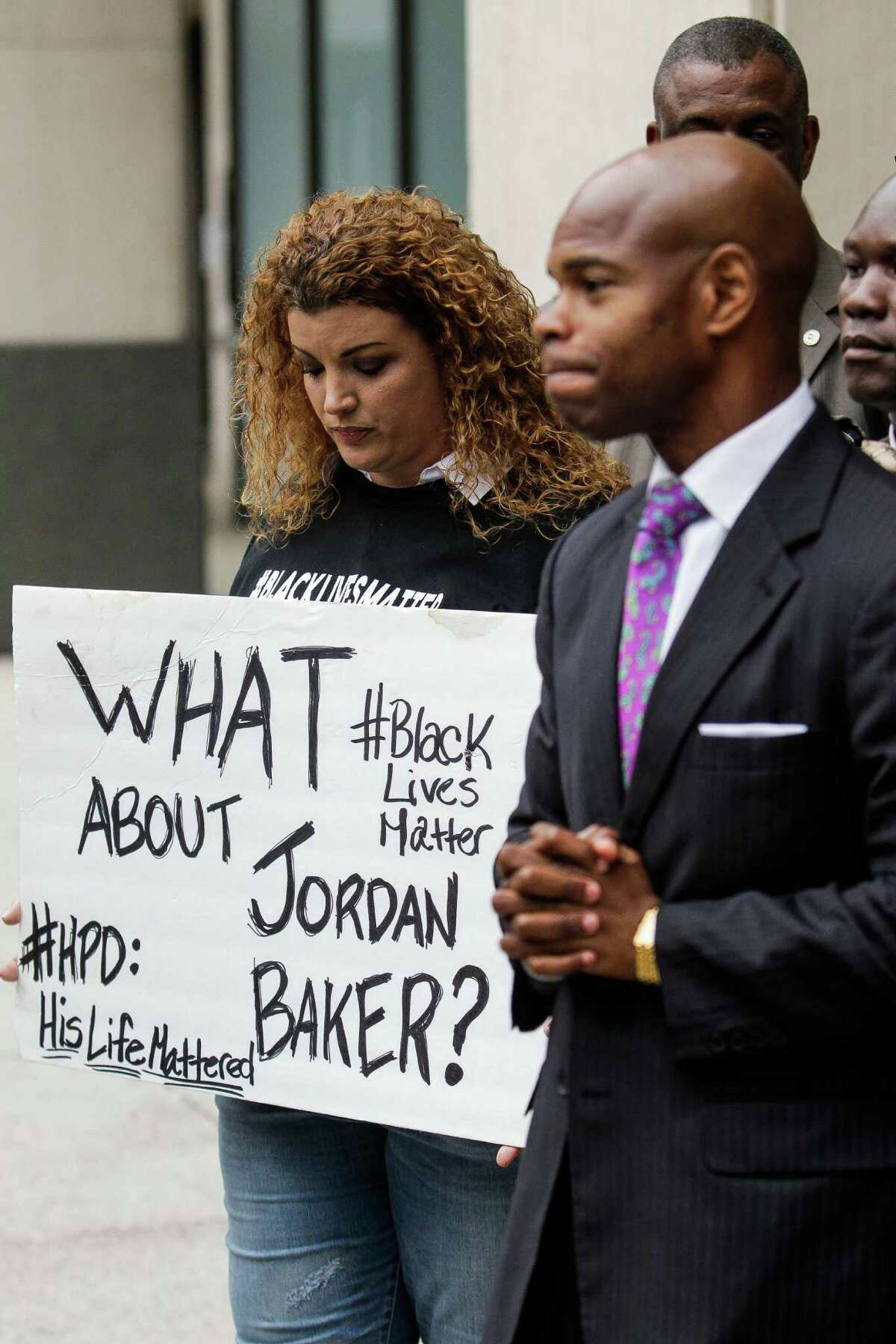 Shere Dore, left, holds a sign as activist Deric Muhammad holds a press conference with other members of the black community to demand the Houston Police Department release a video of the Jordan Baker arrest video Monday, Nov. 30, 2015, in Houston.