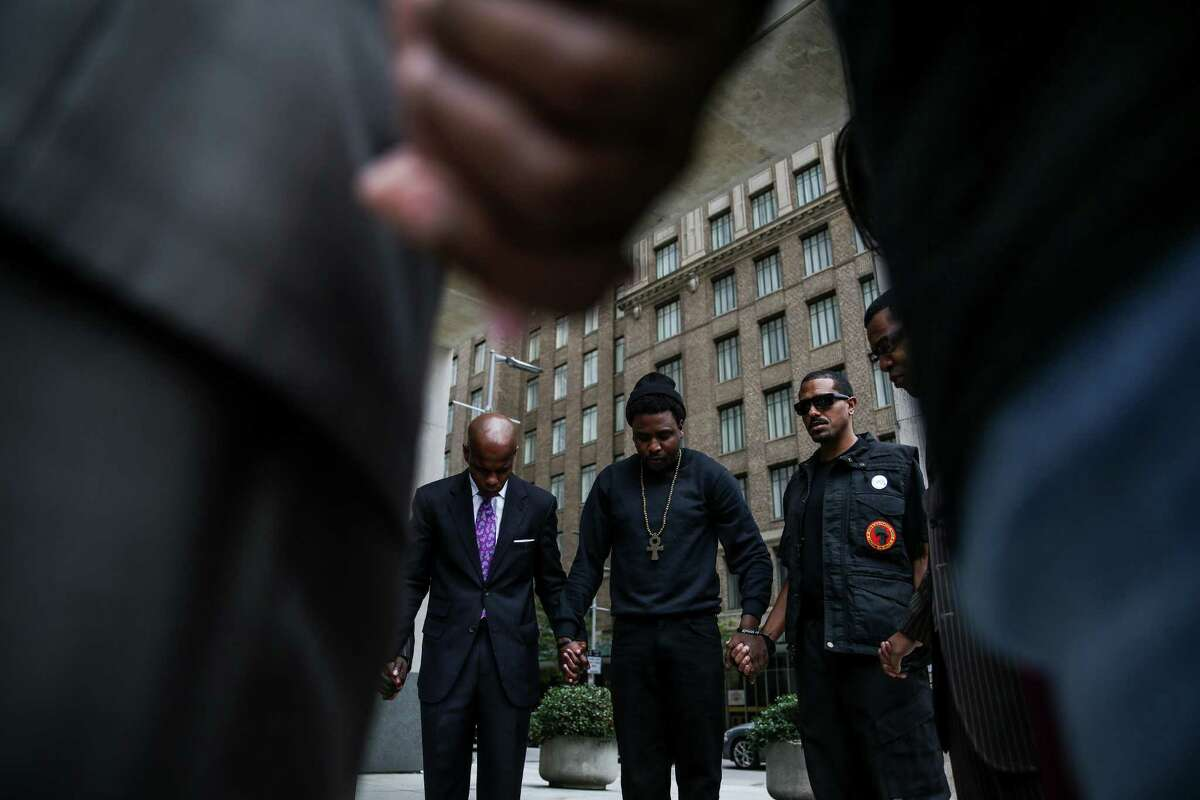 Activist Deric Muhammad, left, Saeed Rose, center, and New Black Panther Party member Desmond, who refused to give his last name, holds hands in prayer after a press conference to demand the Houston Police Department release a video of the Jordan Baker arrest video Monday, Nov. 30, 2015, in Houston.