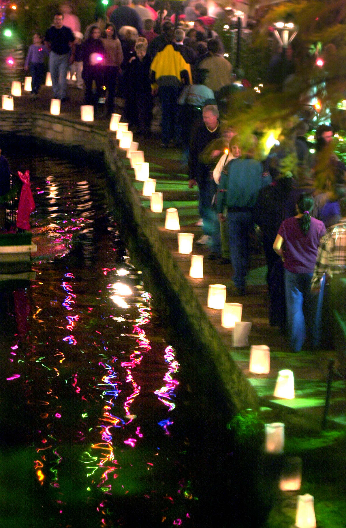 Luminarias light the way on the Riverwalk near the Commerce Street Bridge during the holiday season. Numerous volunteers are needed to fill bags with sand and light the candles.
