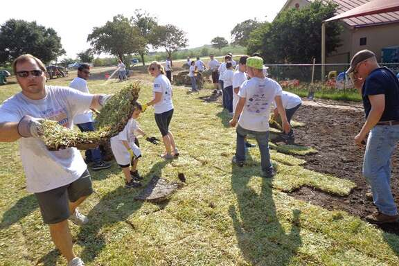 DaVita teammate Chuck Curry helps lays sod at Boysville on Sept. 26. More than 100 DaVita employees and their families volunteered to help restore the Boysville grounds as part of the United Way of Bexar County's Annual Days of Caring.
