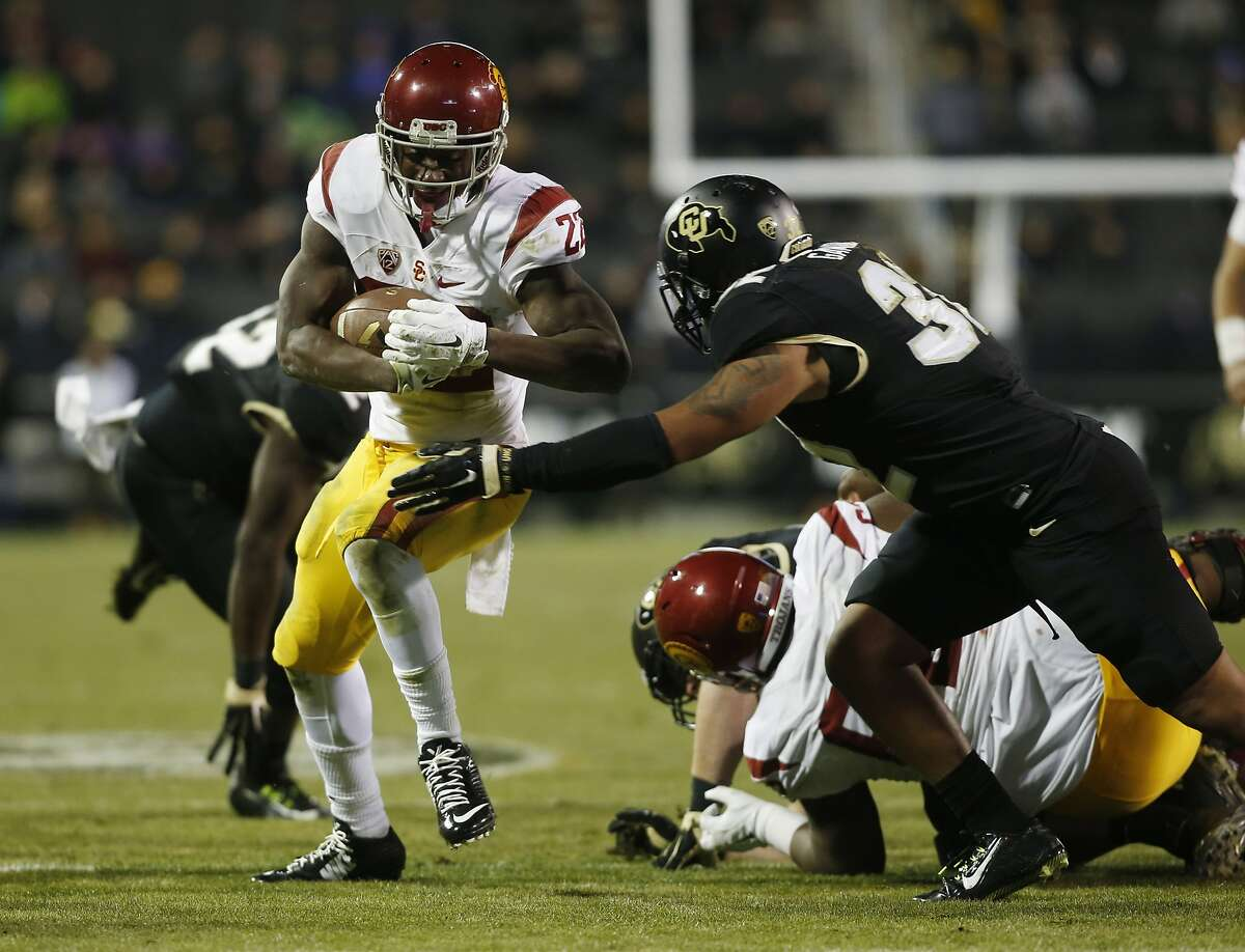 Southern California running back Justin Davis (22), left, runs for a short gain as Colorado linebacker Rick Gamboa (32) comes in for the tackle in the second half of an NCAA college football game Friday, Nov. 13, 2015, in Boulder, Colo. Southern California won 27-24. (AP Photo/David Zalubowski)