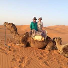 Rob Coons And Jennifer Hofmann and Brownie the Camel in Erg Chebbi Dunes of the Sahara desert in Merzouga, Morocco.
