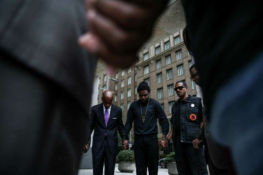 Activists Deric Muhammad, from left, Saeed Rose, and New Black Panther Party member Desmond, who refused to give his last name, pray after a protest Monday, Nov. 30, 2015, to demand that the Houston Police Department release a video of Jordan Baker's arrest. Baker was shot and killed in 2014 by an off-duty HPD officer. Photo: Michael Ciaglo, Staff / © 2015  Houston Chronicle
