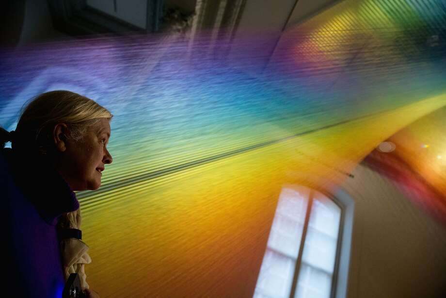 Jocelyn Cox of Chevy Chase, Md., admires a large weaving meant to depict rays of light entitled Plexus A1 by artist Gabriel Dawe, Monday, Nov. 30, 2015, at the newly reopened Renwick Gallery in Washington. It is a visual representation of the full spectrum of natural light, a harnessing of a prismatic view of sunshine that has been confined within the four walls of a gallery space.  Photo: Andrew Harnik, Associated Press