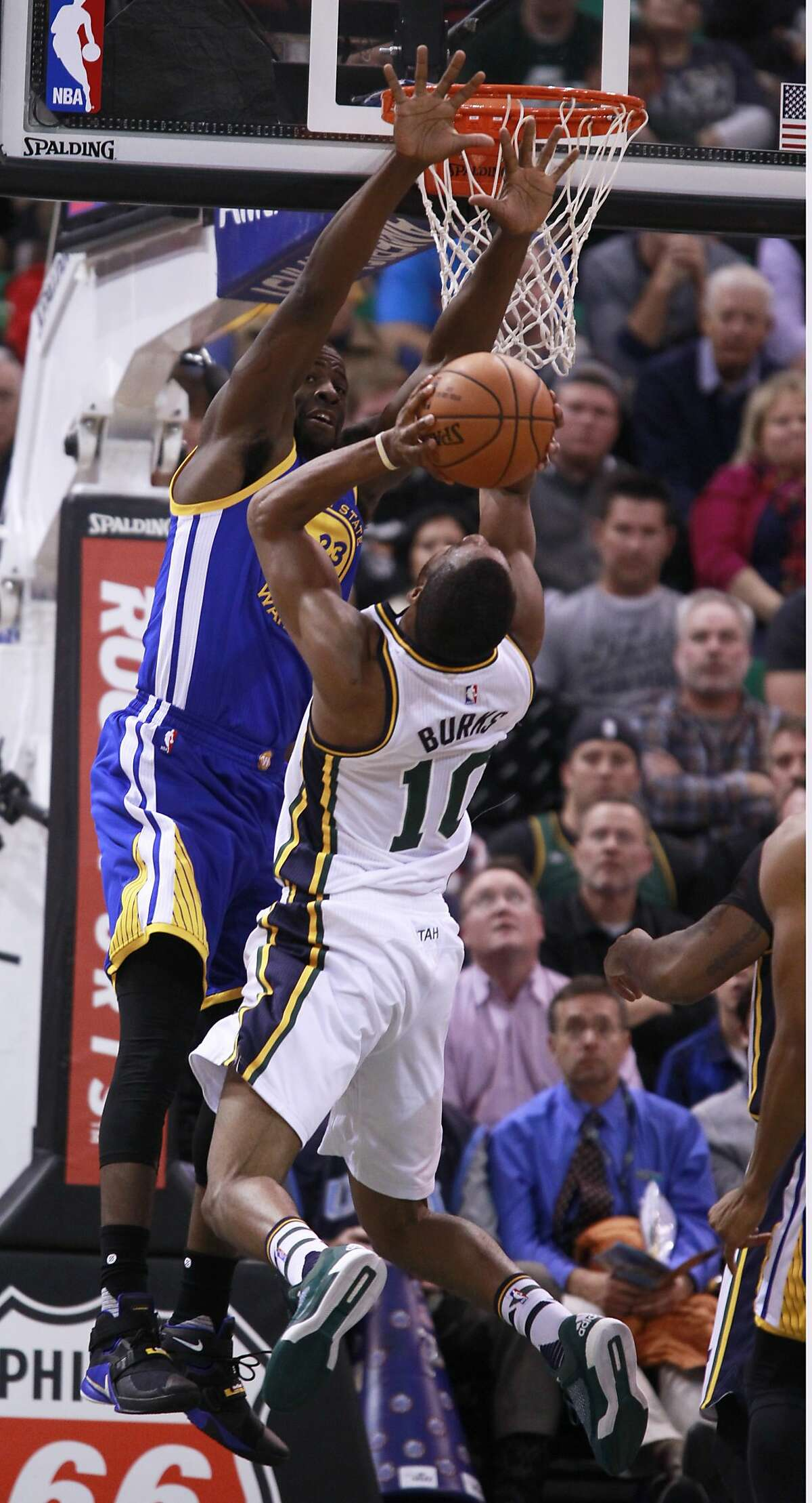 Guard Alec Burks #10 of the Utah Jazz tries to shoot over forward Draymond Green #23 of the Golden State Warriors during the first half of an NBA game November 30, 2014 at Vivint Smart Home Arena in Salt Lake City, Utah.