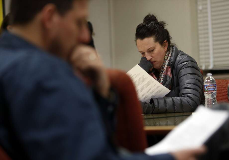 Melrose Leadership Academy parents Kiera Swan (right) and Ian Hetzner (left) read over proposed school assignment changes during community meeting at Roosevelt Middle School in Oakland, Calif., on Monday, November 30, 2015. Photo: Scott Strazzante, The Chronicle