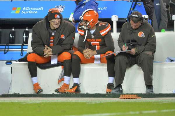 Cleveland Browns quarterbacks Johnny Manziel, left, and Austin Davis, center, talk beside offensive coordinator John DeFilippo in the third quarter of an NFL football game against the Baltimore Ravens Monday, Nov. 30, 2015, in Cleveland. Baltimore won 33-27.