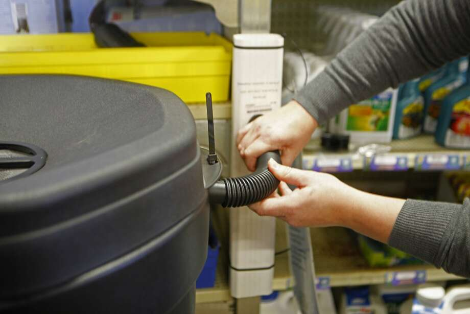 Jennifer Titus at The Urban Store shows the tubing for the overflow connection on a 50 gallon rain barrel on December 1, 2015. Photo: Franchon Smith, The Chronicle