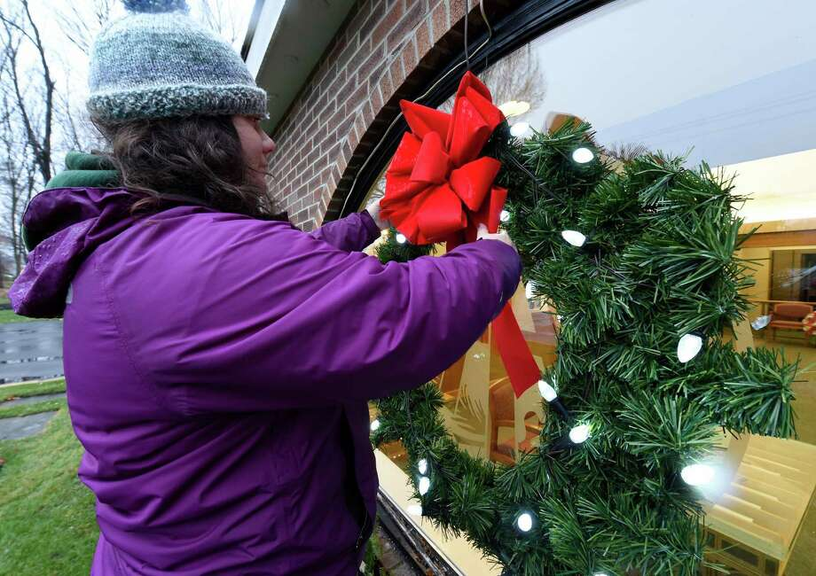 Kelli Mishoe of Dehn's Flowers braves the inclement weather to decorate the face of the Adirondack Trust Bank Tuesday afternoon Dec. 1, 2015 in Malta, N.Y.     (Skip Dickstein/Times Union) Photo: SKIP DICKSTEIN