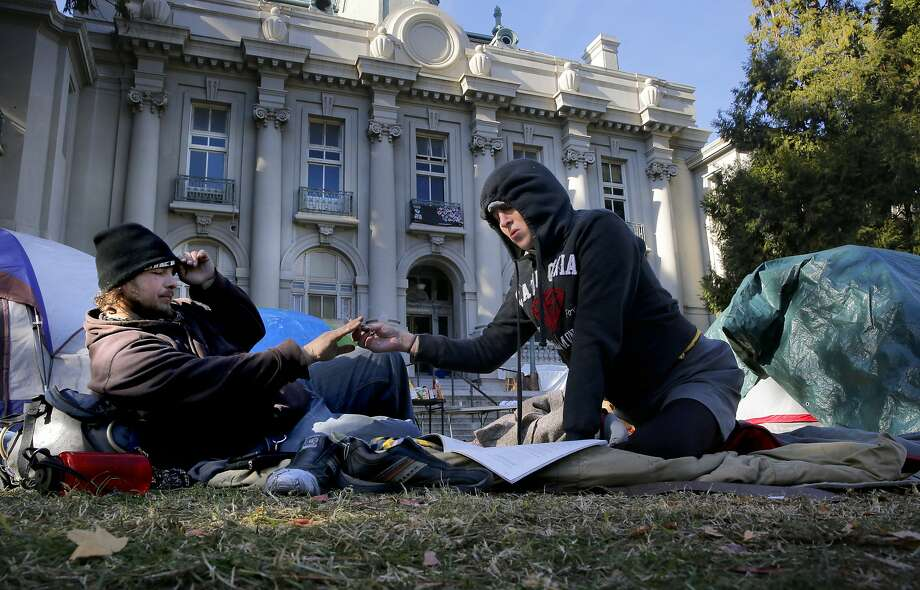 Toby Nixon and Kat, (declined to give her last name) share a cigarette as they join other homeless who have taken over the front lawn outside old City Hall as seen on Tues. December 2, 2015, in Berkeley, Calif., to protest the new homeless ordinances which are up for a final vote tonight before the Berkeley City Council. Photo: Michael Macor, The Chronicle