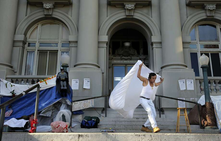 A homeless man, who identifies himself as a street theater artist and goes by the name Ronald Reagan, joins others squatting in front of Old City Hall in Berkeley. Photo: Michael Macor, The Chronicle