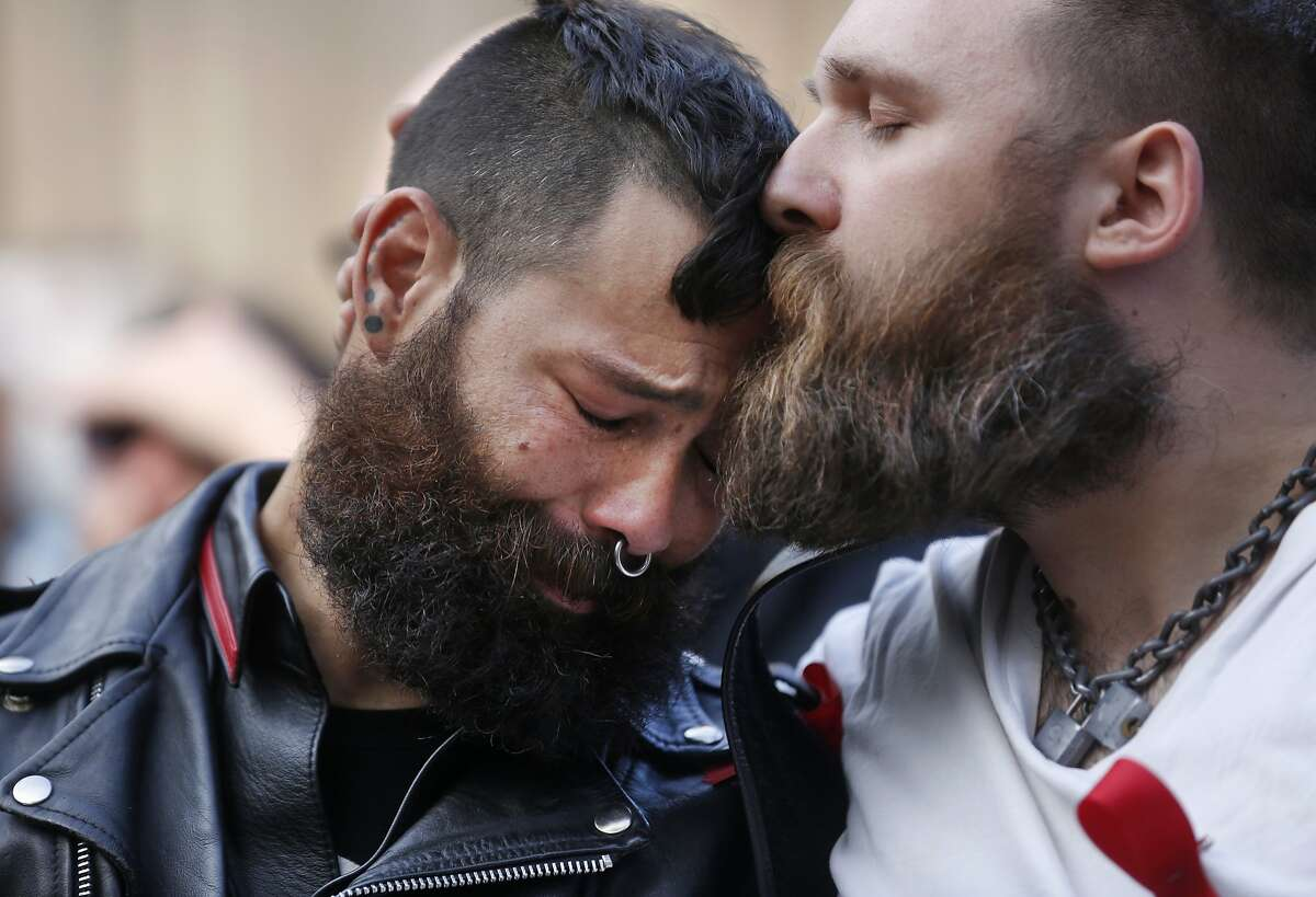 San Francisco Leather Community members Jorge Vieto, left, is kissed on the forehead by Alexi Othenin-Girard, one of his boys, as they watch a video presentation during the 2015 World AIDS Day National Observance ceremony at the National AIDS Memorial Grove Dec. 1, 2015 in Golden Gate Park, San Francisco, Calif. The Thom Weyland Unsung Hero award was presented to the San Francisco Leather community and it was accepted by Vieto on their behalf. Six young people received the Pedro Zamora Young Leaders Scholarship Award. During the ceremony, the National Leadership Recognition honor was presented to former CEO of Levi Strauss & Co. Robert D. Haas.