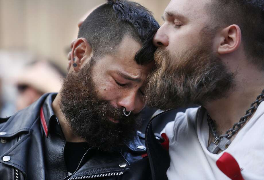 San Francisco Leather Community members Jorge Vieto, left, is kissed on the forehead by Alexi Othenin-Girard, one of his boys, as they watch a video presentation during the 2015 World AIDS Day National Observance ceremony at the National AIDS Memorial Grove Dec. 1, 2015 in Golden Gate Park, San Francisco, Calif. The Thom Weyland Unsung Hero award was presented to the San Francisco Leather community and it was accepted by Vieto on their behalf. Six young people received the Pedro Zamora Young Leaders Scholarship Award. During the ceremony,  the National Leadership Recognition honor was presented to former CEO of Levi Strauss & Co. Robert D. Haas. Photo: Leah Millis, The Chronicle