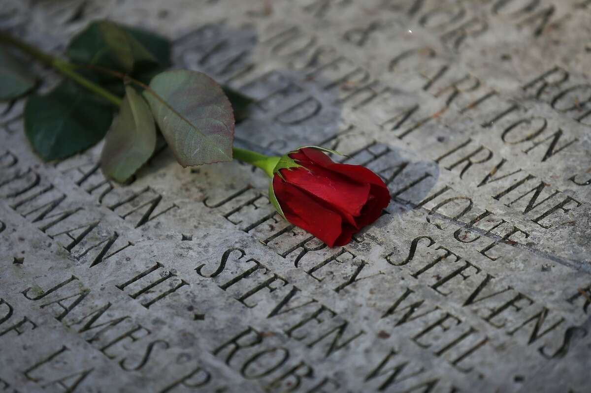A rose lays on top of the names inscribed in the Circle of Friends memorial at the National AIDS Memorial Grove in Golden Gate Park.