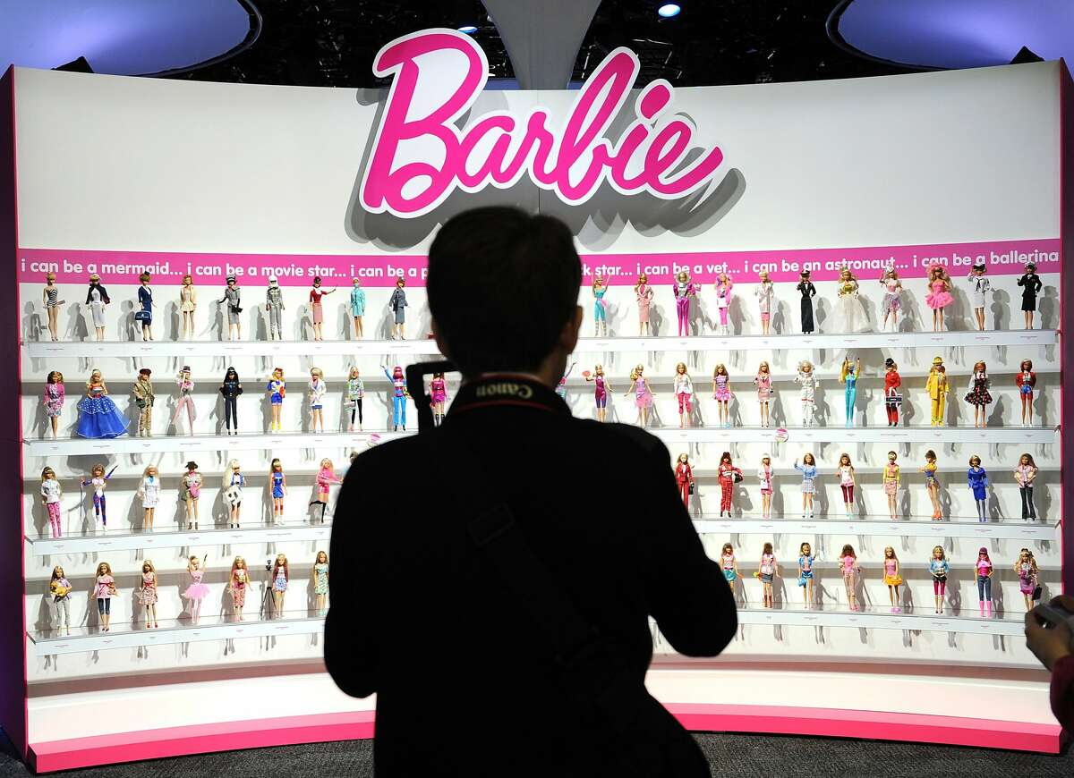 """(FILES) In this February 14, 2010 file photo, a woman photographs a wall of Barbie dolls in the Mattel display at the annual Toy Fair, in New York. The new Barbie doll is """"intelligent"""" and connected. Too connected for some privacy activists. The high-tech """"Hello Barbie"""" doll unveiled earlier this year by toy giant Mattel and likely to be a holiday hit allows children to speak and get a response from their favorite toy. But to make that happen, conversations travel over Wi-Fi networks to Internet """"cloud"""" servers that use artificial intelligence to deliver a personal reply. For the activist group Campaign for a Commercial-Free Childhood, the privacy risks of the intelligent Barbie outweigh the benefits. """"Children confide in dolls and reveal intimate details about their lives, but Hello Barbie won't keep those secrets,"""" the group said in a statement November 30, 2015. AFP PHOTO/Stan HondaSTAN HONDA/AFP/Getty Images"""