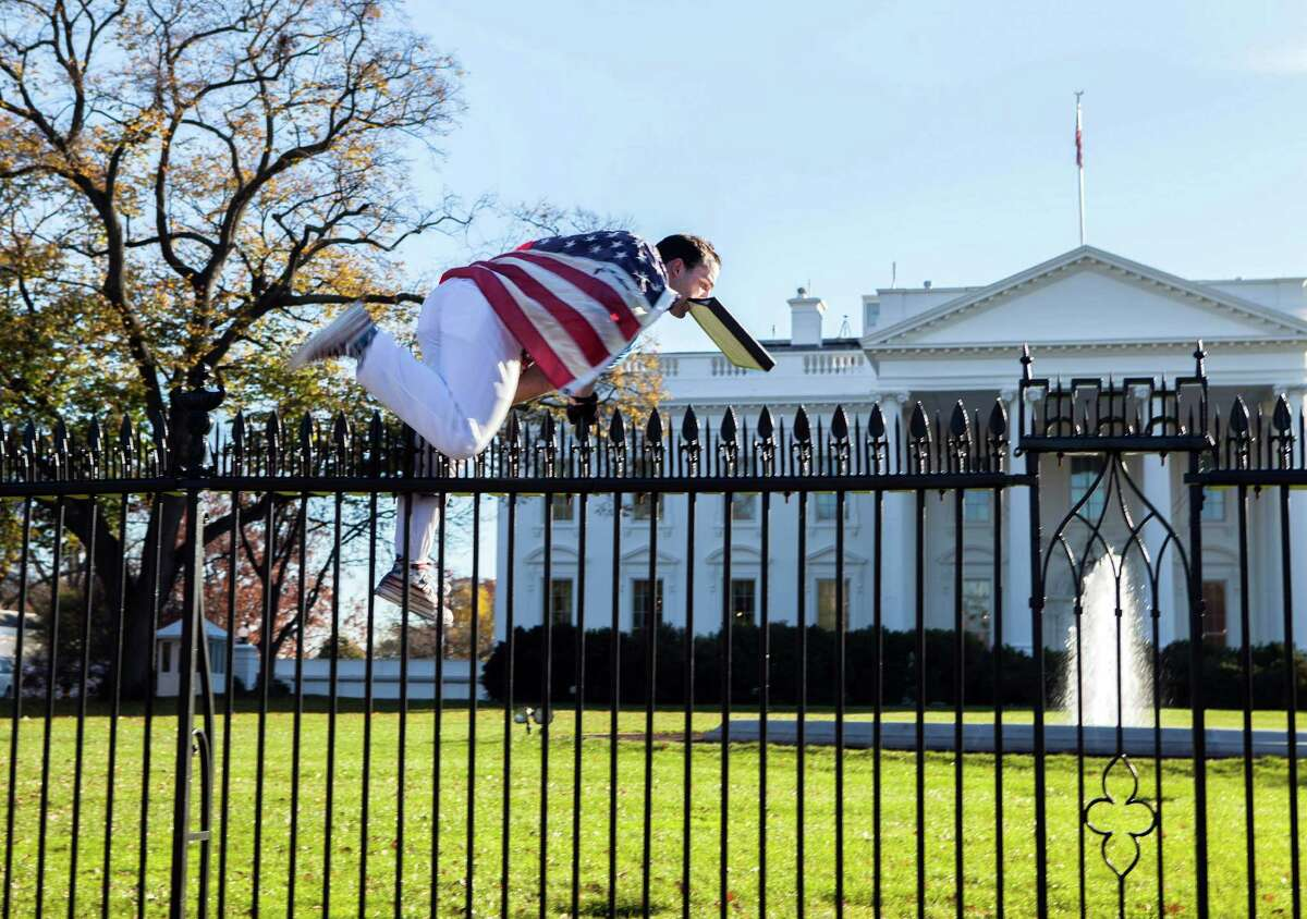 In this photo provided by Vanessa Pena, Joseph Caputo jumps a fence at the White House on Thursday.