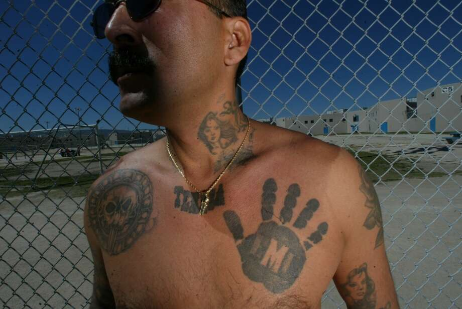 "Black hand of the Mexican MafiaNicknamed the ""black hand of death"" according to former gangster Rene Enriquez, this tattoo is an identifier for members of the Mexican Mafia. Enriquez told NPR in 2008 that the Mexican Mafia was one of the most influential gangs of California, having infiltrated nearly every prison in the state.  Photo: Bob Chamberlin, LA Times Via Getty Images"