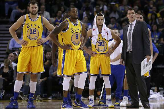 From left, Golden State Warriors' Andrew Bogut, Andre Iguodala, Stephen Curry, and interim head coach Luke Walton during the second half of an NBA basketball game Tuesday, Nov. 17, 2015, in Oakland, Calif. (AP Photo/Ben Margot)